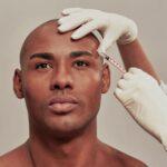 Mann während Behandlung Stirn