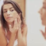 schöne Frau vor Spiegel prüft Hautunreinheiten