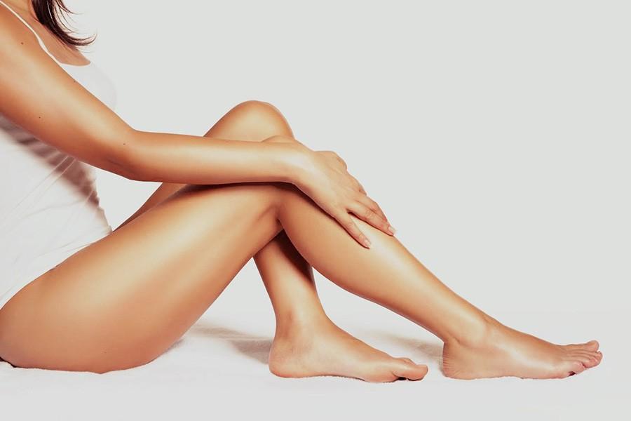 Sitzende Frau mit schönen, gepflegten und glatten Beinen